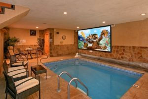 Skinny Dippin is a luxury one bedroom cabin in Pigeon Forge with a heated indoor pool, theater in pool, fire pit, quality furnishings, and incredibly convenient location in Pigeon Forge