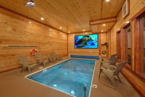 Splash Mountain Lodge is a four bedroom rental cabin in Pigeon Forge with an indoor pool, theater room, arcade, and mountain view